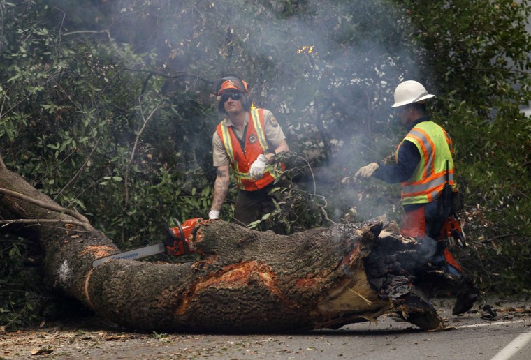 California State Park employees use chainsaws to remove a smoldering tree that fell on Highway 1 during a wildfire in Big Sur, California, December 17, 2013. Crews battling the wildfire along central California's scenic Big Sur coastline were on guard against a possible shift in winds on Tuesday, after the blaze destroyed at least 15 dwellings and forced 100 people to flee their homes, fire and county officials said. (REUTERS/Michael Fiala)