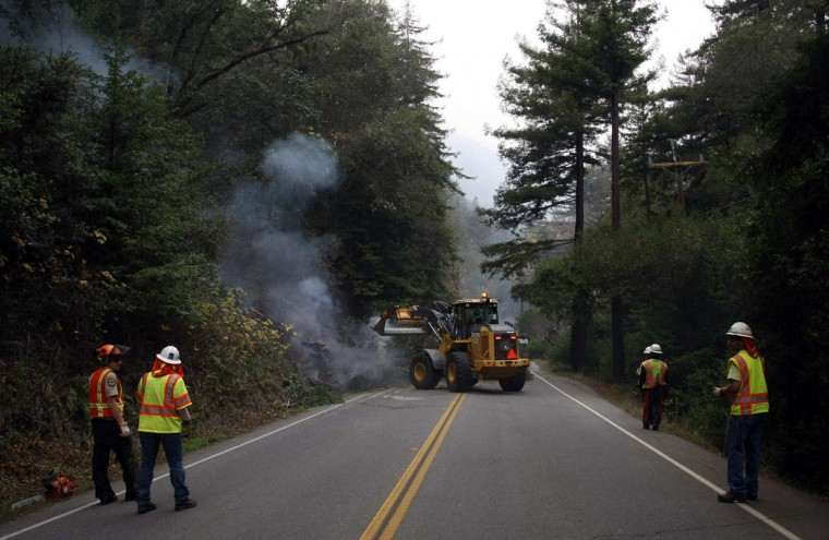 Crews remove a smoldering tree that fell on Highway 1 during a wildfire in Big Sur, California, December 17, 2013. Crews battling the wildfire along central California's scenic Big Sur coastline were on guard against a possible shift in winds on Tuesday, after the blaze destroyed at least 15 dwellings and forced 100 people to flee their homes, fire and county officials said. (REUTERS/Michael Fiala)