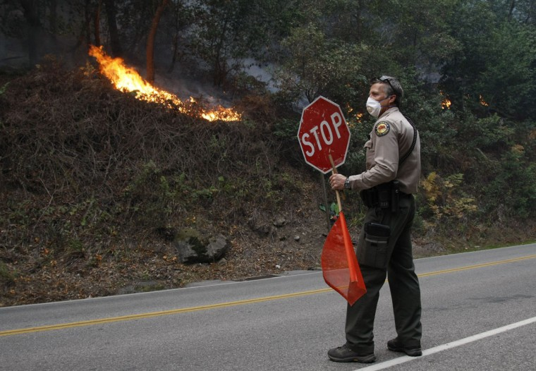 State Park Ranger Phil Bergman stops traffic on Highway 1 after a tree fell on the road as a result of a wildfire in Big Sur, California, December 17, 2013. Crews battling a wildfire along central California's scenic Big Sur coastline were on guard against a possible shift in winds on Tuesday, after the blaze destroyed at least 15 dwellings and forced 100 people to flee their homes, fire and county officials said. (REUTERS/Michael Fiala)