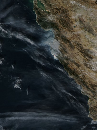 The smoke and heat from the Pfeiffer Fire near Big Sur, California is captured on December 16, 2013 by MODIS or Moderate Resolution Imaging Spectroradiometer instrument that flies aboard NASA's Aqua satellite. The red outlined area represents the heat from the fire. Crews battling a wildfire along central California's scenic Big Sur coastline were on guard against a possible shift in winds on Tuesday, after the blaze destroyed at least 15 dwellings and forced 100 people to flee their homes, fire and county officials said. (REUTERS/NASA Goddard MODIS Rapid Response Team)