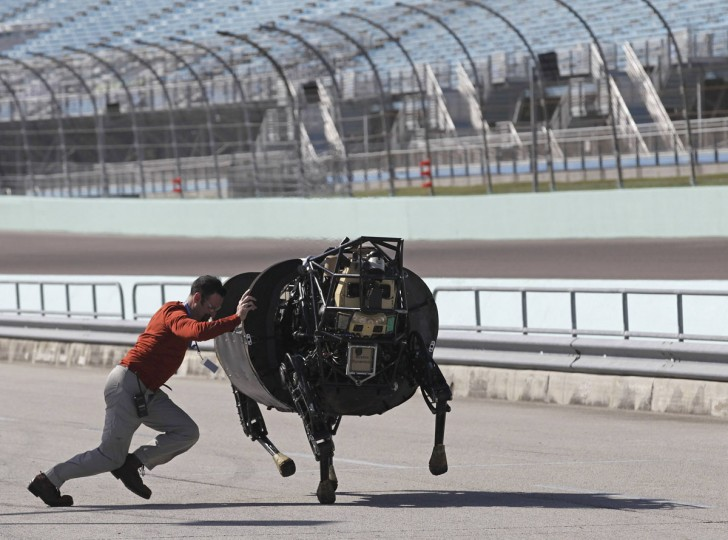 An unidentified LS3 team member shoves an LS 3 (Legged Squad Support System) robot that was galloping off course, back on track during a high-speed demonstration in Homestead, Florida December 20, 2013. The device is designed to accompany soldiers and Marines any place they go on foot, helping to carry their gear. The south Florida city is hosting an international Robotics Challenge Trials this weekend, organized by the U.S. Defense Advanced Research Projects Agency. The competition, for the creation of robots that can respond to natural and man-made disasters, was created following the 2011 Fukushima-Daiichi nuclear power plant disaster in Japan. After the disaster the Pentagon sent robots designed to disarm improvised explosive devices in Iraq to try to help fix problems at the destroyed reactor in areas highly contaminated by radioactive releases where humans could not work. (REUTERS/Andrew Innerarity)