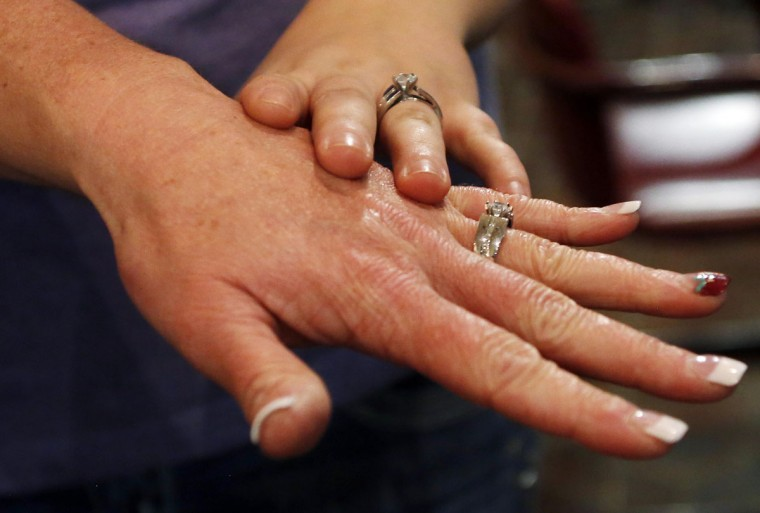 Shauna Griffen (left) and Brooke Shepherd show their rings after getting married at the Salt Lake County Government Building in Salt Lake City, Dec. 23, 2013. U.S. District Judge Robert Shelby in Utah on Monday refused to block his own order making same-sex marriage legal in the state, denying a request to do so by Governor Gary Herbert. (Jim Urquhart/Reuters)