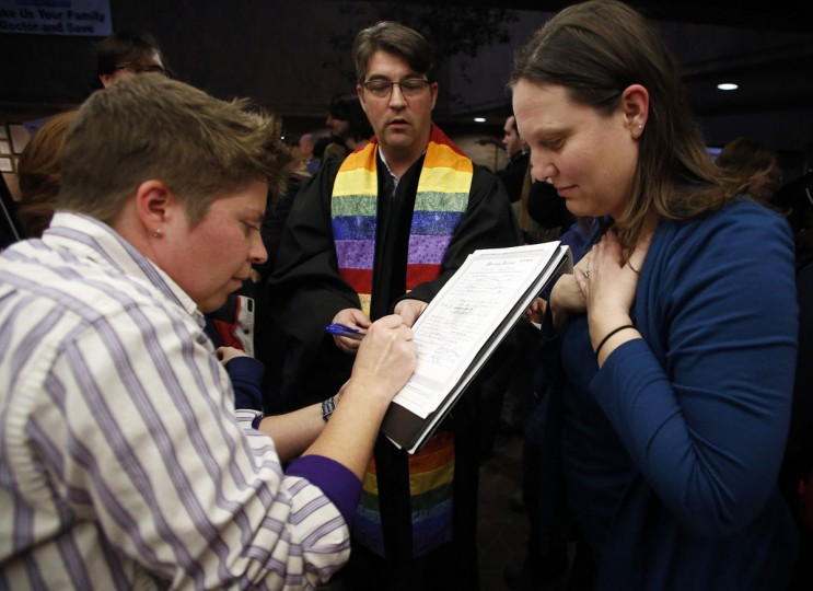 Ruth (left) and Kim Hackford-Peer sign their marriage certificate after getting married as Reverend Curtis Price watches at the Salt Lake County office building in Salt Lake City. (Jim Urquhart/Reuters)