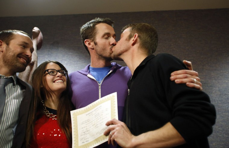 The first gay couple to be married in Utah, Michael Ferguson (second from right) and his husband Seth Anderson kiss as Blake Ferguson (left) and his girlfriend Danielle Morgan watch. The pair married at the Salt Lake County clerk's office in Salt Lake City, after a federal judge on Friday struck down Utah's ban on same-sex marriage on Dec. 20, 2013. (Jim Urquhart/Reuters)