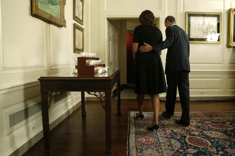 U.S. President Barack Obama and first lady Michelle Obama depart after observing a moment of silence and lighting candles in memory of the 20 children and six school workers killed by a gunman at Sandy Hook Elementary School one year ago, in the Map Room at the White House in Washington, December 14, 2013. Obama marked the anniversary of the Newtown, Connecticut, school shootings on Saturday by calling for tighter gun control and expanded mental health care. (REUTERS/Jonathan Ernst)