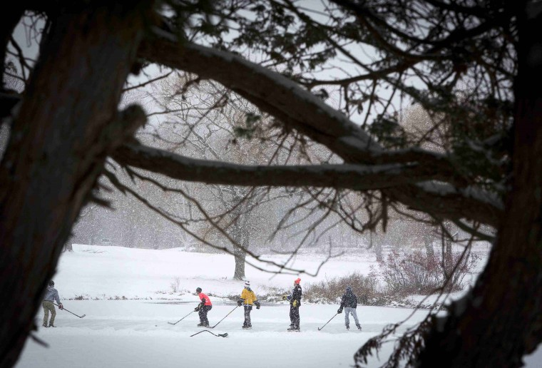 A group of local residents plays a game of shinny hockey on a frozen pond in Newtown, Connecticut December 14, 2013. Locals have been striving to return to normal even as today marks the one year anniversary of the shooting rampage at Sandy Hook Elementary School, where 20 children and six adults were killed by gunman Adam Lanza. (REUTERS/Carlo Allegri)