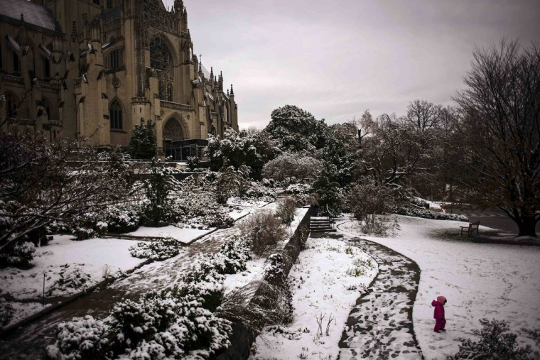 A child plays in the snow in the garden of the National Cathedral in Washington December 10, 2013. (James Lawler Duggan/Reuters)