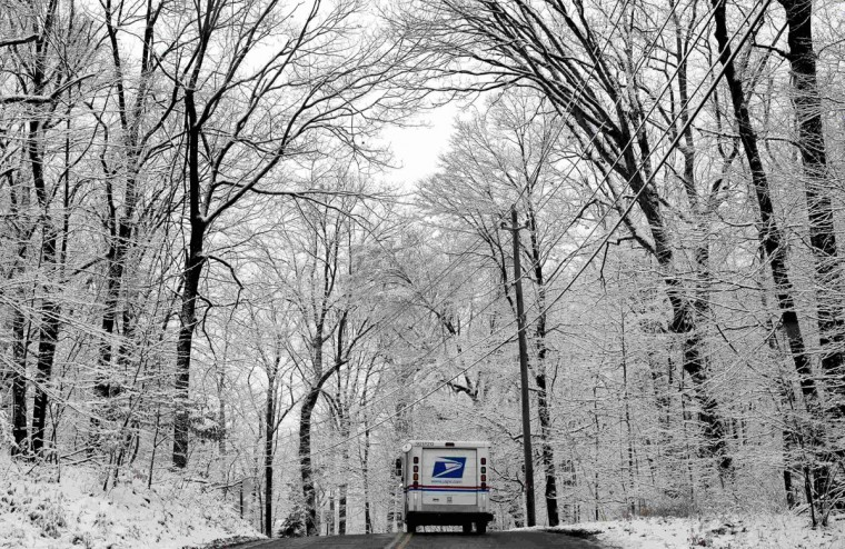 A U.S. Mail delivery truck drives beneath snow covered trees along Clausland Mountain Road in the New York City suburb of Orangeburg, N.Y. (REUTERS / Mike Segar)