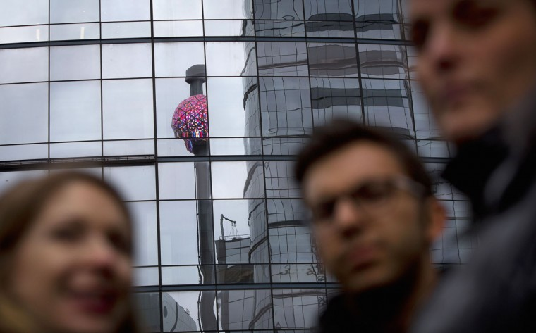 People watch as workers test the ball that will drop at midnight in Times Square, ahead of New Year's Eve celebrations in New York December 30, 2013. (REUTERS/Carlo Allegri)