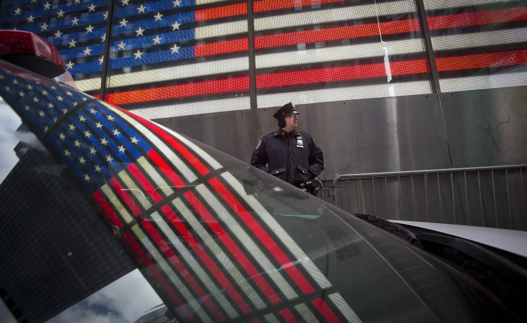 The U.S. flag is reflected in the window of a police car as a police man stands guard in Times Square ahead of New Year's Eve celebrations in New York, December 31, 2013. Security has been stepped up in the area around where the celebrations will take place. (REUTERS/Carlo Allegri)
