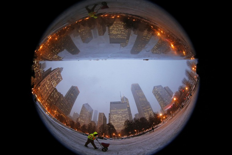 "A worker is reflected in the mirrored sculpture ""Cloud Gate,"" also commonly known as ""The Bean,"" as he sprinkles de-icing salt around the bean-shaped sculpture in Chicago, Illinois, December 16, 2013. Picture taken with a fish-eye lens. (Jim Young/Reuters)"