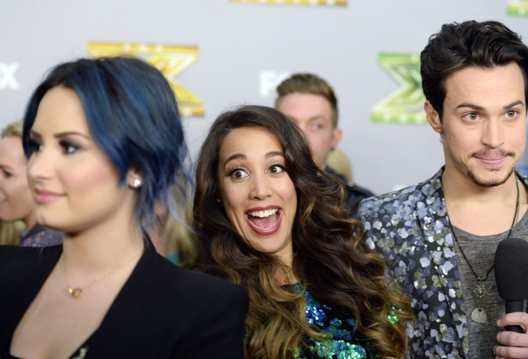 "Sierra Deaton (C) photobombs judge Demi Lovato's interview as Alex Kinsey (L) speaks to a television reporter backstage after the folk duo won ""The X Factor "" in Los Angeles, California, December 19, 2013. Winners Kinsey and Deaton won a $1 million recording contract with Sony Music Entertainment. (REUTERS/Kevork Djansezian)"