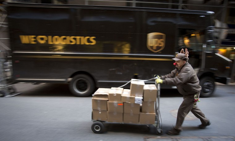 UPS delivery man Vinny Ambrosino prepares to deliver packages on Christmas Eve while wearing a Rudolf nose and antlers in New York, December 24, 2013. (REUTERS/Carlo Allegri)