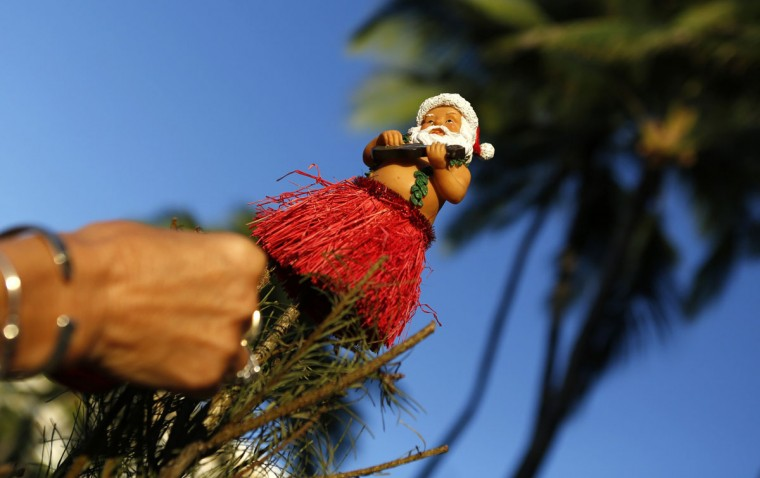 A Hawaiian Santa ornament sits atop a Christmas tree being decorated by Staci Kennedy, of Cape Cod, Massachusetts, on Waikiki Beach in Honolulu, Hawaii December 25, 2013. Kennedy and her friends have been taking part in this Christmas day festivity for 16 years. (Kevin Lamarque/Reuters)