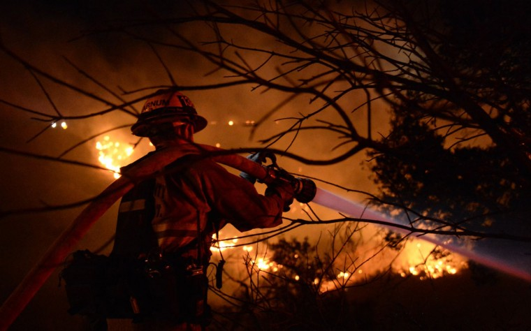 A firefighter battles a Christmas night brush fire in Simi Valley, California late December 25, 2013. Strong winds helped the brush fire burn along Santa Susana Pass Rd, just west of Rocky Peak, south of the 118 freeway. The cause of the fire is still under investigation, according to local media. (REUTERS/Gene Blevins)