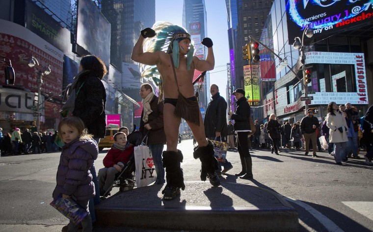 "Adam David (C) poses for tips as ""The Naked Indian"" as people walk past in Times Square in New York, December 28, 2013. (REUTERS/Carlo Allegri)"
