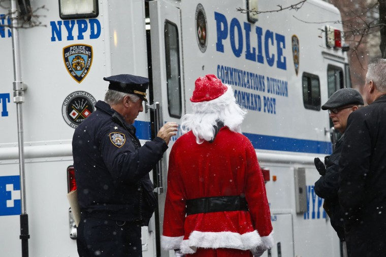 An NYPD police officer speaks with a reveller dressed as Santa Claus during the SantaCon event in New York December 14, 2013. Every year since 1997, thousands of men and women have dressed up as Santas, elves, reindeer or some other holiday confection and descended on the city's streets for a daylong bar crawl that begins with good cheer and, for many, inevitably ends in a blurry booze-soaked haze. Many come from Long Island and New Jersey, getting a head start on the festivities on the train ride into the city. (REUTERS/Eduardo Munoz)