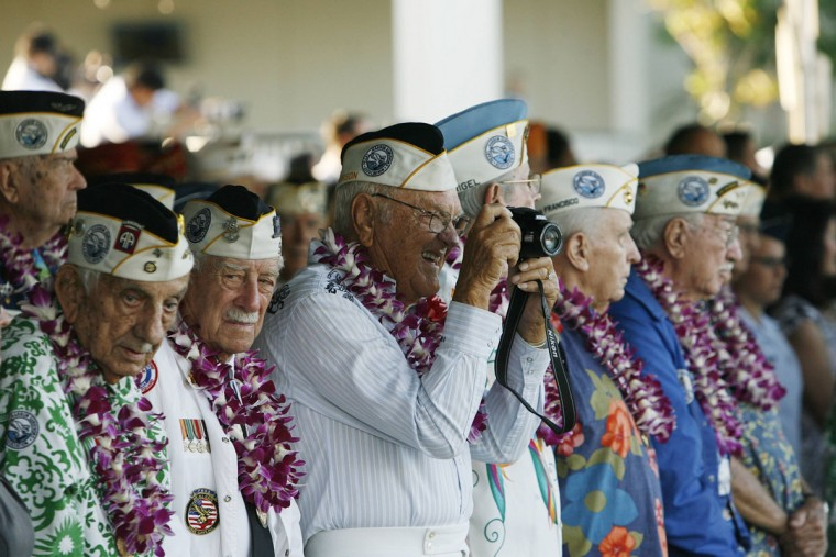 Pearl Harbor survivor Ewalt Schatz takes a picture as the USS Halsey gets ready to pass the Arizona Memorial during the 72nd anniversary of the attack on Pearl Harbor at the WW II Valor in the Pacific National Monument in Honolulu, Hawaii on December 7, 2013. (REUTERS/Hugh Gentry)