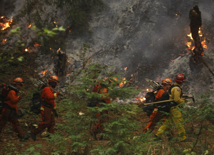 A firefighting crew walks past burning trees in Big Sur, California, December 16, 2013. According to local media, a wildfire in Monterey County grew to more than 500 acres on Monday and some 300 firefighters were deployed to battle the blaze in the Big Sur area. (REUTERS/Michael Fiala)