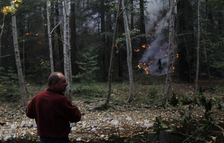 A visitor watches as a wildfire burns along the Big Sur River in Big Sur, California, December 16, 2013. According to local media, the wildfire in Monterey County grew to more than 500 acres on Monday and some 300 firefighters were deployed to battle the blaze in the Big Sur area. (REUTERS/Michael Fiala)