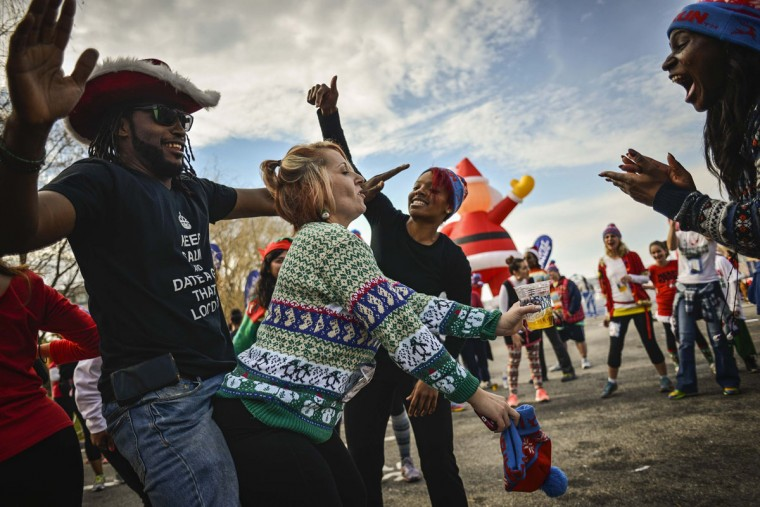 Runners dance at the finish line of the Ugly Sweater Run at National Harbor in Fort Washington, Maryland December 21, 2013. (REUTERS/James Lawler Duggan)