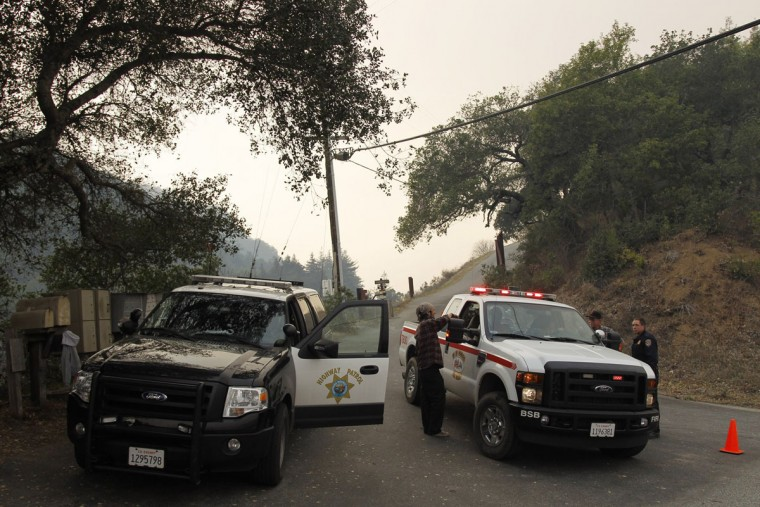 Police and fire vehicles sit at an access road that leads to an area where a wildfire is burning in Big Sur, California, December 16, 2013. According to local media, the wildfire in Monterey County grew to more than 500 acres on Monday and some 300 firefighters were deployed to battle the blaze in the Big Sur area. (REUTERS/Michael Fiala)