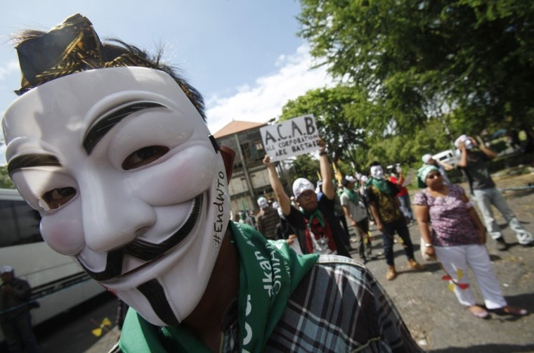 A protester from the Youth Movement of Indonesia Caravan wearing a Guy Fawkes mask gets ready to take to the streets along with other protesters ahead of the ninth World Trade Organization (WTO) Ministerial Conference in Denpasar, on the Indonesian resort island of Bali December 3, 2013. The WTO conference will begin on Tuesday until Friday. (Edgar Su/Reuters)