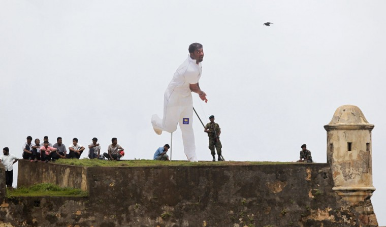 Spectators and soldiers, from behind a cut-out of Sri Lanka's Muttiah Muralitharan, watch the third day's play in the first test cricket match between Sri Lanka and India from the top of a fort overlooking the grounds on July 20, 2010. (REUTERS/Andrew Caballero-Reynolds)