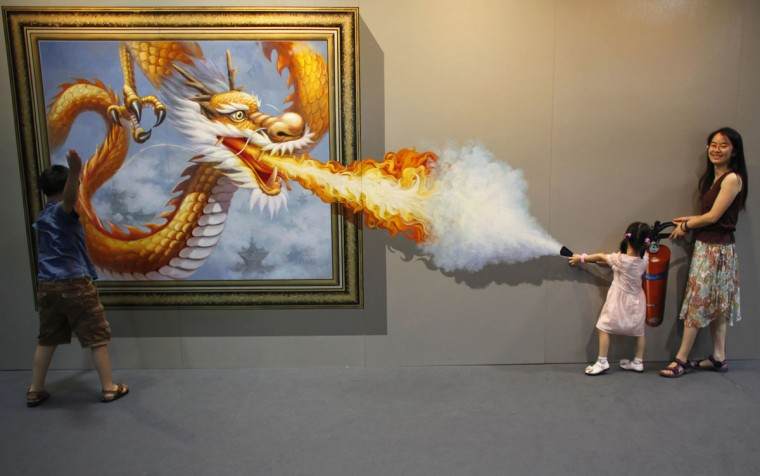 Members of a family pose for a photograph in front of a 3D painting at the 2012 Magic Art Special Exhibition in Hangzhou, Zhejiang province on July 7, 2012. (REUTERS / Carlos Barria)