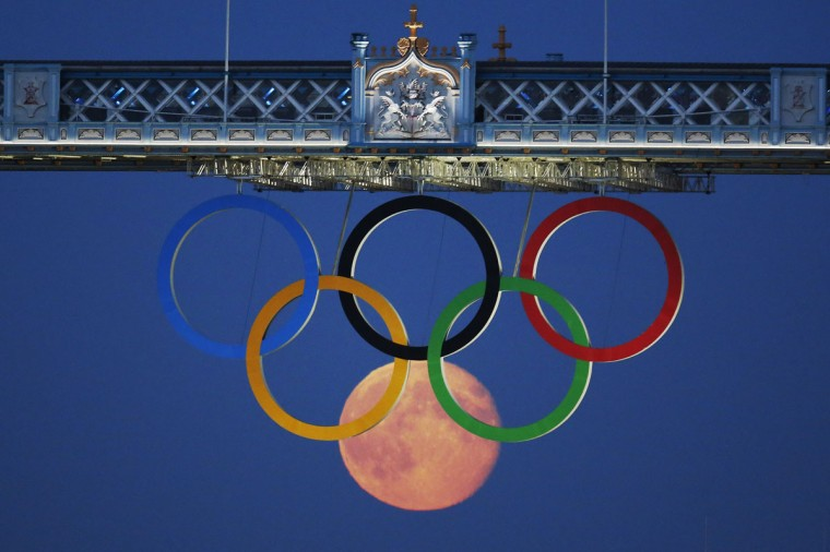 The full moon rises through the Olympic Rings hanging beneath Tower Bridge during the London 2012 Olympic Games on August 3, 2012. (REUTERS / Luke MacGregor)