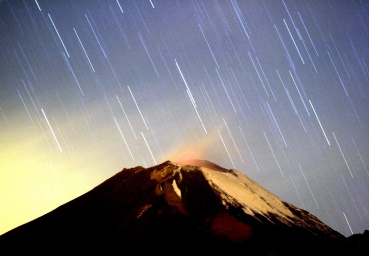 A meteor streaking past stars, light up the night sky over the Mexican volcano Popocatepetl near the village San Nicolas de los Ranchos in Mexican state of Puebla in the early hours of December 14, 2004. The shower, named Geminid because it appears to originate from the constellation Gemini, lit up the sky with dozens of shooting stars per hour. (Daniel Aguilar/Reuters)