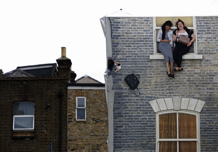 "Visitors are seen in a reflection as they pose on Argentine artist Leonardo Erlich's optical illusion installation ""Dalston House"" in east London on June 26, 2013. The artwork, commissioned by the Barbican Gallery, uses mirrors to create the impression of a house on which people can play and pose for visual effect. (REUTERS / Luke MacGregor)"