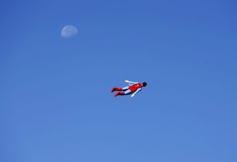 A radio-controlled Superman plane, flown by designer Otto Dieffenbach, passes the moon during a test flight in San Diego on June 27, 2013. (REUTERS / Mike Blake)
