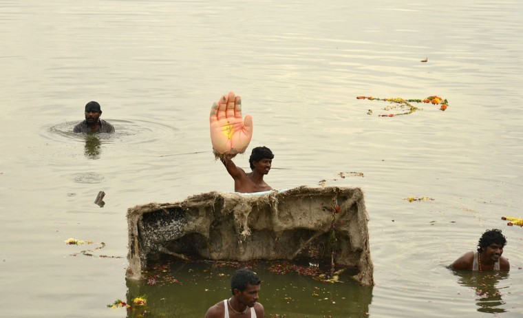 A man holds the hand of an idol of the Hindu elephant god Ganesh, the deity of prosperity, during idol immersion ceremony in the Hussain Sagar lake during the Ganesh Chaturthi festival in the southern Indian city of Hyderabad on September 17, 2013. (REUTERS / Krishnendu Halder)