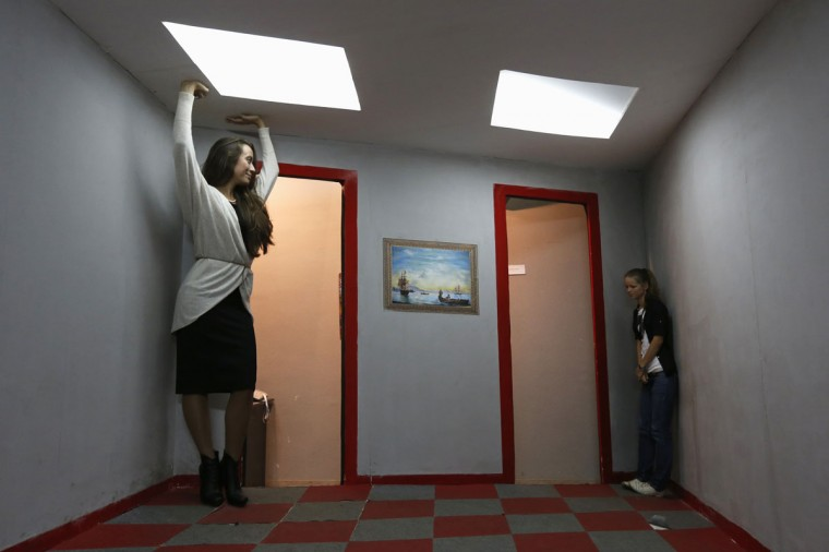 Visitors look at each other in an Ames room at a private exhibition of optical Illusions in St. Petersburg on September 24, 2013. An Ames room is constructed with a distorted perspective to confuse observers' sense of scale. (REUTERS / Alexander Demianchuk)