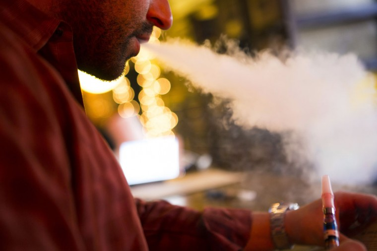 A customer puffs on an e-cigarettes at the Henley Vaporium in New York City December 18, 2013. At the Henley Vaporium, one of a growing number of e-cigarette lounges sprouting up in New York and other U.S. cities, patrons can indulge in their choice of more than 90 flavors of nicotine-infused vapor, ranging from bacon to bubble gum. (Mike Segar/Reuters)