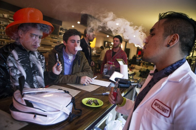 "An employee ""Vapologist"" (right) stands behind the bar as he puffs on an e-cigarette with customers at the Henley Vaporium in New York City December 18, 2013. (Mike Segar/Reuters)"