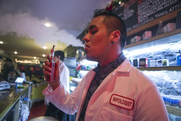 "An employee ""Vapologist"" stands behind the bar as he puffs on an e-cigarette with customers at the Henley Vaporium in New York City December 18, 2013. At the Henley Vaporium, one of a growing number of e-cigarette lounges sprouting up in New York and other U.S. cities, patrons can indulge in their choice of more than 90 flavors of nicotine-infused vapor, ranging from bacon to bubble gum. (Mike Segar/Reuters)"