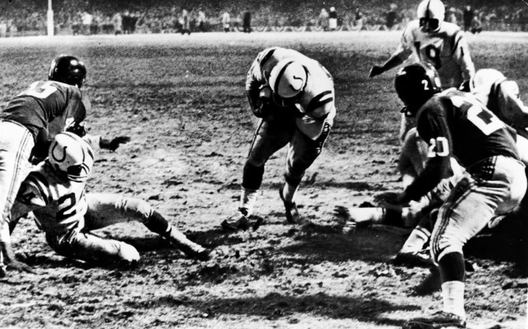 This is a view from New York Giant's side, showing Baltimore Colts' fullback, Alan Ameche, going through a big hole provided by teammates to score the winning touchdown in overtime period at Yankee Stadium, December 28, 1958. Colts' Lenny Moore gets a good block on Giants' Emlen Tunnell (45) at left. Colt quarterback Johnny Unitas (19) is at right along with Giants' Jim Patton (20), Baltimore beat New York 23-17 for 1958 pro football title. It was Colts' first championship, and the first overtime finish in title history. (File photo)