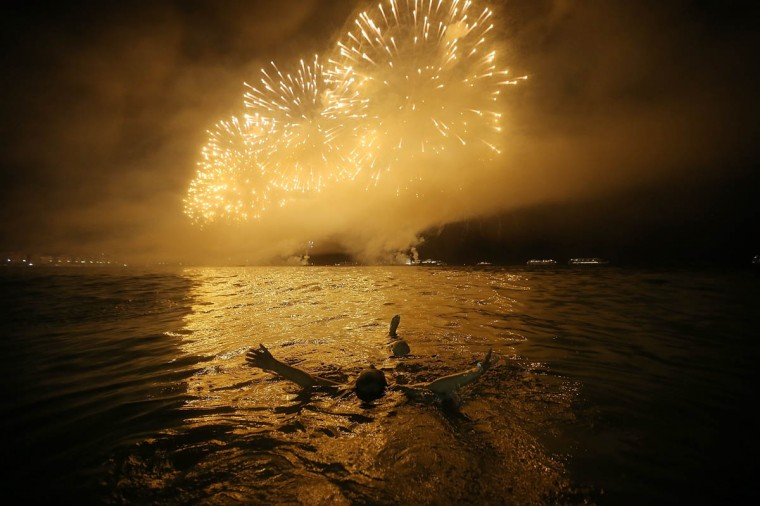 A reveler floats while watching fireworks explode minutes after midnight along Copacabana Beach during New Year's celebrations in Rio de Janeiro, Brazil. More than two million were expected to attend the celebrations at Copacabana to ring in 2014. Brazil is gearing up to host the 2014 FIFA World Cup and the Rio 2016 Olympic Games. (Mario Tama/Getty Images)