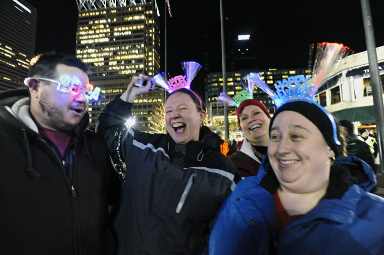 Dani Dillon, center, of Gaithersburg, cheers to the music of Alter Ego as she and fiancee Tony Dillon, from left, and friends, Alex Sepesy, of D.C., and Kristina Sullivan, of Silver Springs, celebrate New Year's eve at the Inner Harbor to welcome in 2014. (Kenneth K. Lam/Baltimore Sun)