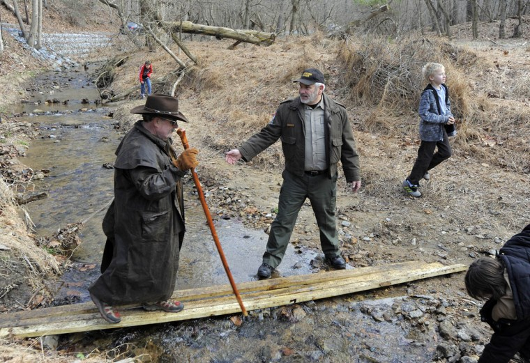 Earl Breyette, left, of Lewisberry,PA. gets some help from Max Buffington a volunteer ranger that was leading the hike through Patapsco Valley Park. . The State Department of Natural Resources kicks off 2014 with First Day Hikes. This one is in the Patapsco Valley State Park's Daniels area. (Lloyd Fox/Baltimore Sun)