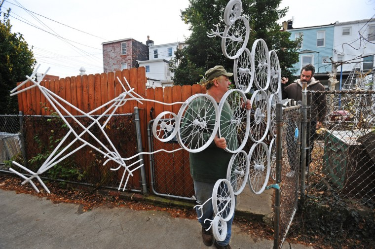 Helped by his friend, Zach Titford (right), metal artist Jim Pollock prepares to decorate his rowhouse in the 700 block of W. 34th Street in Hampden. (Kenneth K. Lam/Baltimore Sun)