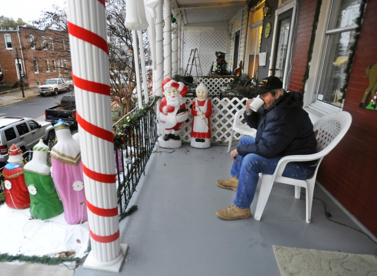 "Jerry Jackson, a resident of the 700 block of W. 34th Street in Hampden, takes a break as he sets up holiday decorations for the ""Miracle on 34th Street"" display. (Kenneth K. Lam/Baltimore Sun)"