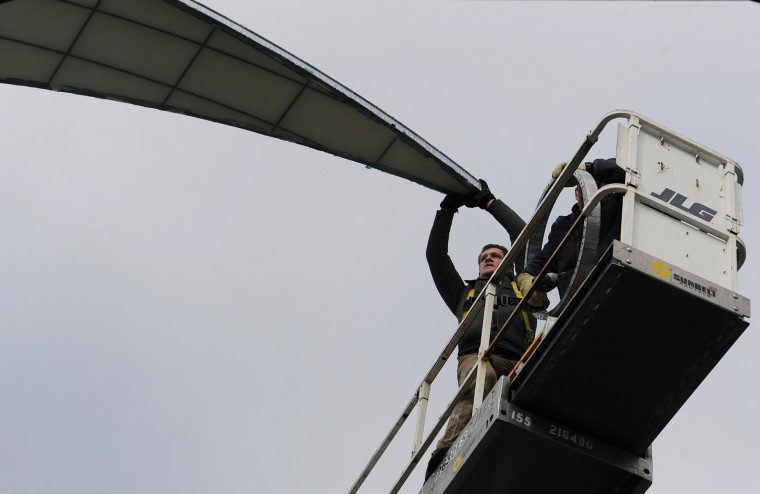 Trevor Morrison holds on as he and his crew remove the last panel of the dome on Wednesday afternoon. (Jon Sham/BSMG)