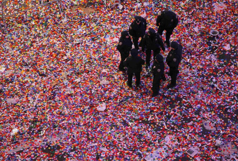 Police officers stand in confetti after it was dropped on revelers at midnight during New Year's Eve celebrations in Times Square in New York. (Gary Hershorn/Reuters photo)