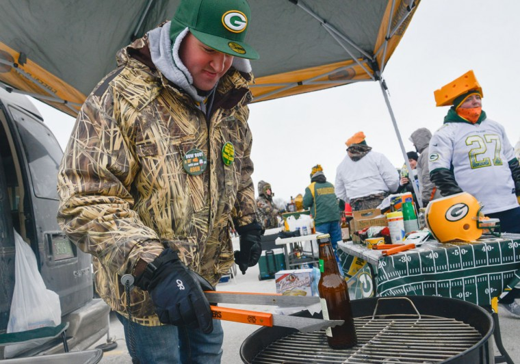 Jon Eiseoe attempts to thaw a beverage bottle prior to the game between the Green Bay Packers and the San Francisco 49ers during the 2013 NFC wild card playoff football game at Lambeau Field.(Benny Sieu/USA Today Sports)