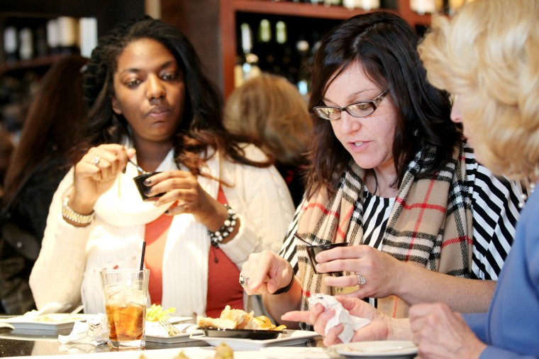 Assistant to Chief of Staff in the County Executive Office Malina Colon tastes food with Senior Intern Ife Agwu, left, during the Baltimore County's Winter Restaurant Week Kick-Off event at Liquid Lib's in Timonium on Thursday, Jan. 9, 2014. (Jen Rynda/BSMG)