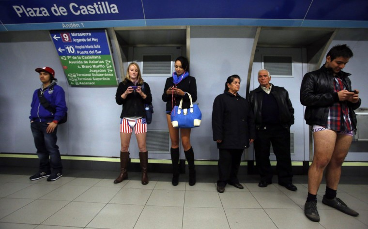 "Passengers without their pants check their mobile phones as they wait for a train during the ""No Pants Subway Ride"" event at Plaza de Castilla subway station in Madrid January 12, 2014. (Sergio Perez/Reuters)"