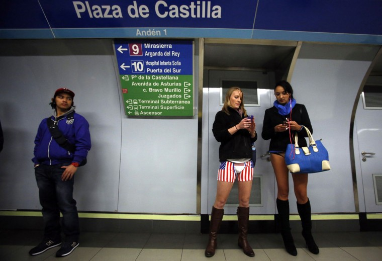 "Passengers without their pants check their mobile phones as they wait for a train during the ""No Pants Subway Ride"" event at Plaza de Castilla subway station in Madrid January 12, 2014. (Sergio Perez/Reuters0"